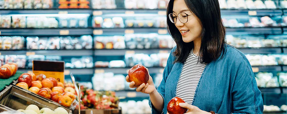 image of a woman choosing apple in supermarket